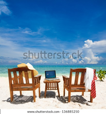 Chairs, laptop and put away tie and white collar shirt. Chairs on the beach on sunny day