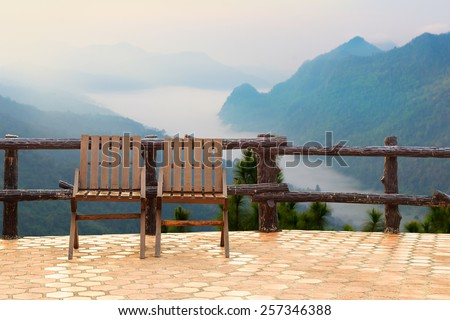 Chairs over mountain  with sky and fog - stock photo