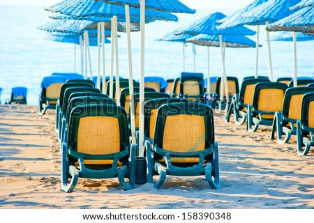 chairs stand in a row under blue umbrellas
