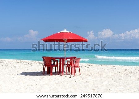 Chairs, table and umbrella on a tropical beach in Cancun, Mexico. - stock photo