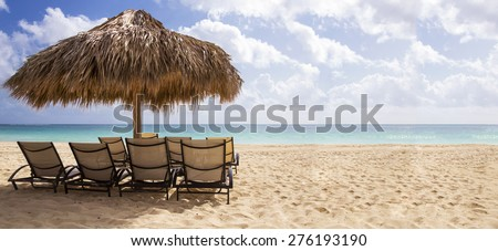 Chairs under Hut on a Caribbean beach over looking the blur and green ocean on a sun drenched day - stock photo