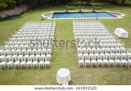 Chairs Wedding Home Outdoors White chairs dozens positioned on grass lawn with swimming pool outdoors for private wedding occasion. - stock photo