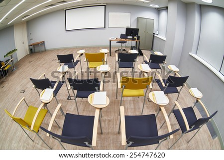 Chairs with notepads in an empty classroom. Fish-eye photo - stock photo