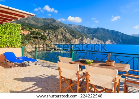 Chairs with table on sunny terrace with sea view on Kefalonia island near Assos village, Greece - stock photo