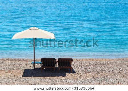 Chaise longue and umbrella on the beach facing the sea - stock photo