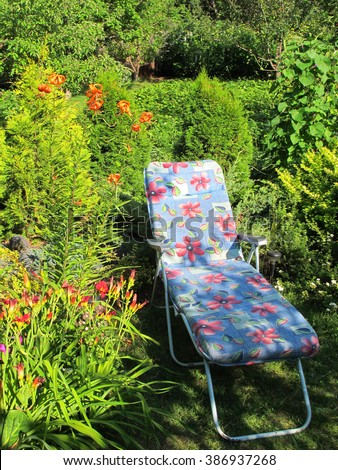 Chaise-longue in the blooming summer sunny garden