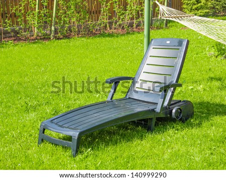 Chaise longue on the green grass in the yard of a country house