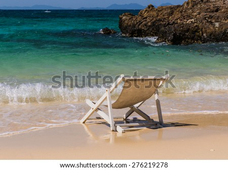 chaise lounge near the sea shore beach - stock photo