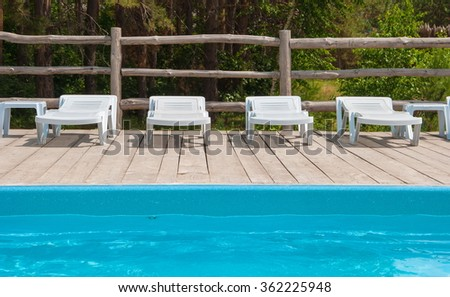 chaise lounges around the pool in the forest recreation area