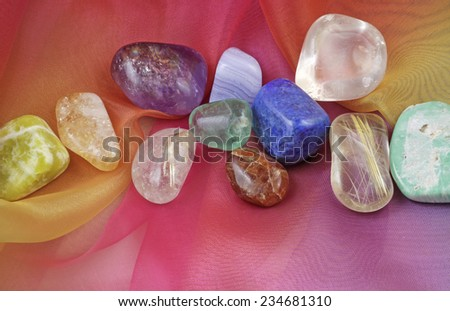 Chakra gemstones on Rainbow Chiffon  -  A selection of tumbled chakra gemstones laying on rainbow chiffon material - stock photo