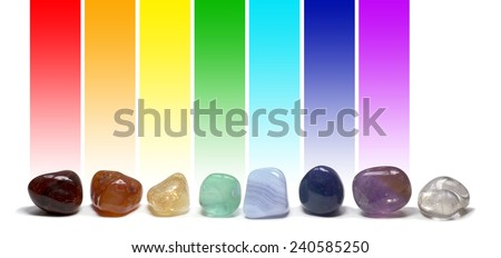 Chakra Healing Crystals -  Row of chakra colored tumbled gem stones in a row on a white background with the corresponding chakra color above each stone - stock photo