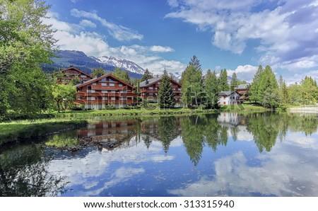 Chalets and lake at Crans-Montana by beautiful day, Valais, Switzerland - stock photo