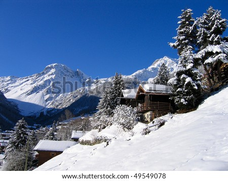 Chalets in a snow white valley in the Swiss Alps on a clear day.