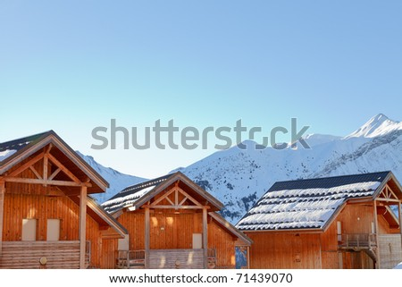 Chalets in snowy mountain landscape with blue sky. France. Alps. - stock photo
