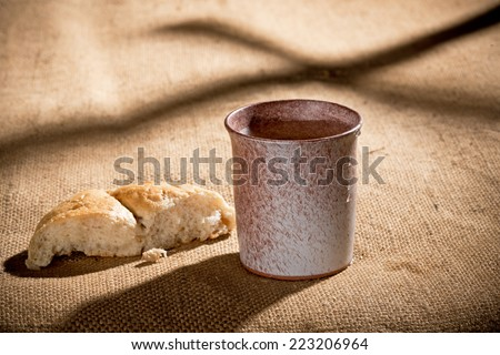 chalice and bread on the textile tablecloth - stock photo