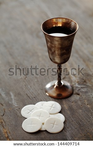 Chalice with wine and communion wafers on wooden background - stock photo