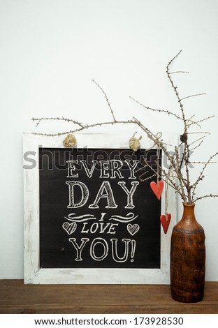 "chalk board saying ""Every day I love you""  with two red vintage hearts and rustic old wooden table and white wall. - stock photo"