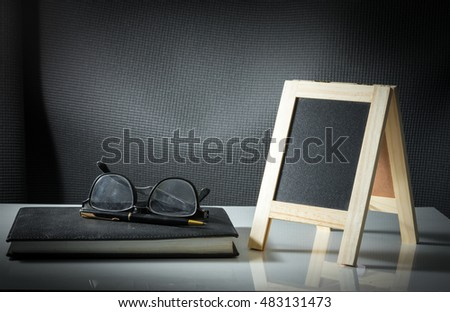 Chalk board with eyeglasses, pen and book.