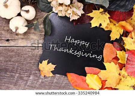 Chalk board with text Happy Thanksgiving surrounded by autumn leaves, flowers and white pumpkins over a rustic background. - stock photo