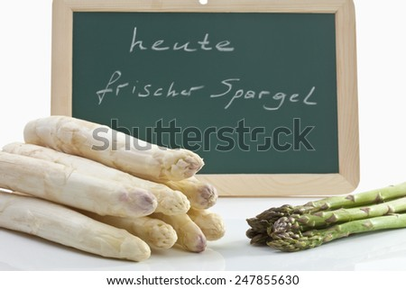 Chalk board with white and green asparagus - stock photo