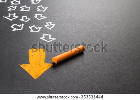 Chalk drawing of orange arrow with many white arrows as follower - stock photo