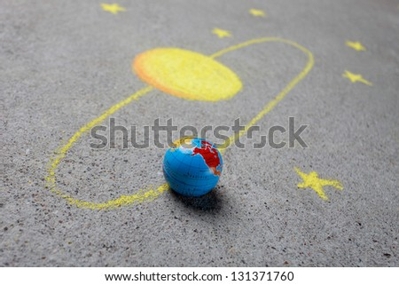 Chalk drawing of sun and a globe - stock photo