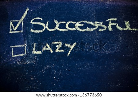 chalk writings on blackboard, choice between being lazy or successful - stock photo