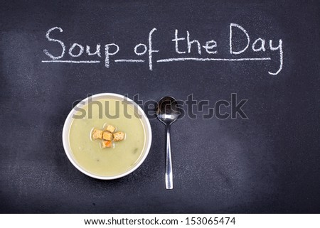 Chalkboard advertising the soup of the day, with a bowl of leek and potato soup and spoon, garnished with bread croutons, and space for your text - stock photo