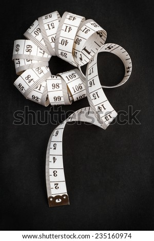 Chalkboard background with a measuring tape - stock photo