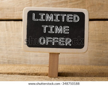 Chalkboard on wooden background with Limited Time Offer words - stock photo