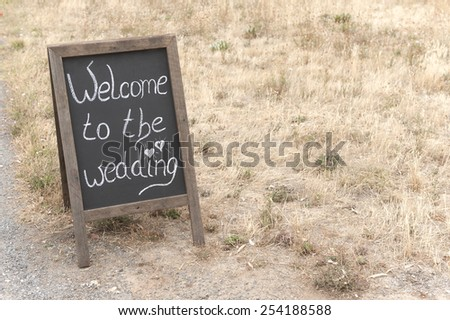 Chalkboard sign welcoming people to the wedding ceremony. - stock photo