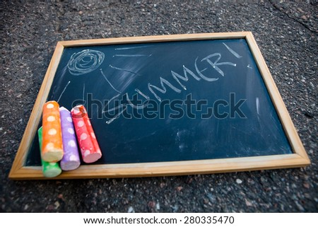 Chalkboard that has summer written on it with a picture of sun and colorful street chalk - stock photo