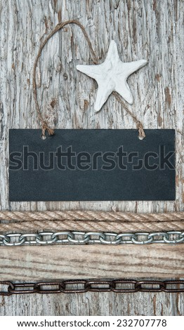 Chalkboard with chain, rope and seashell on the old wood - stock photo