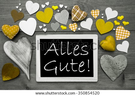 Chalkboard With German Text Alles Gute Means Best Wishes. Many Yellow Textile Hearts. Wooden Background With Vintage, Rustic Or Retro Style. Black And White Image With Colored Hot Spots. - stock photo