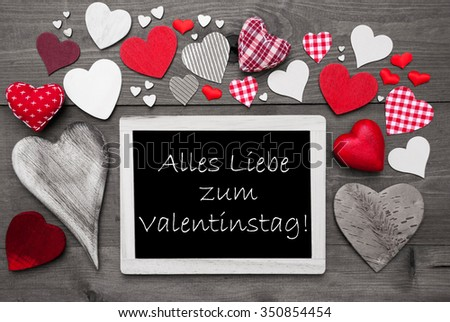 Chalkboard With German Text Alles Liebe Zum Valentinstag Means Happy Valentines Day. Many Red Textile Hearts. Wooden Background With Vintage, Rustic Or Retro Style. Black And White Image. - stock photo