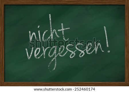 chalkboard with german text nicht vergessen, which means do not forget - stock photo