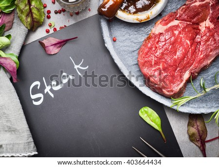 Chalkboard with inscription Steak, raw beef steak and ingredients for grill or BBQ on rustic kitchen table, top view, place for text - stock photo