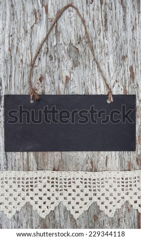 Chalkboard with lacy ribbon on old wood background - stock photo