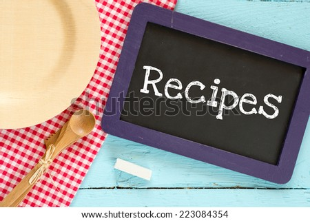 Chalkboard with text recipes. Chalkboard with wooden spoon and plate on a red checkered tablecloth and text recipes - stock photo