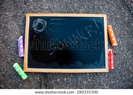 Chalkboard with word summer written on it and a sun with colorful street chalk - stock photo