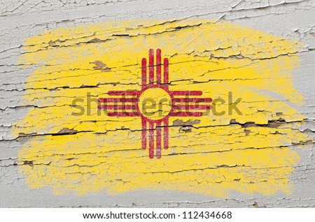 Chalky american state of new mexico flag precisely painted with color chalk on grunge wooden texture - stock photo