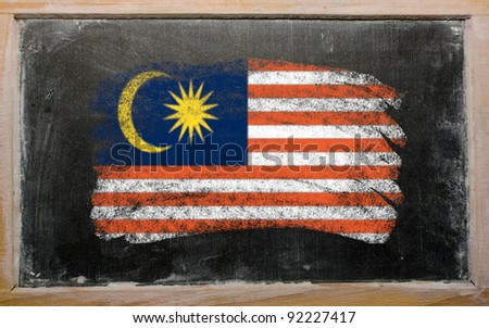 Chalky malaysian flag painted with color chalk on old blackboard - stock photo