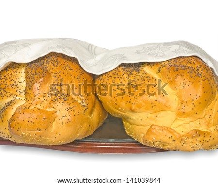 Challah bread for the Jewish Sabbath.Traditional food for a Friday night meal. 2 bread loaves with poppy seeds covered by a white cloth rest on a wood and glass board.Isolated on a white background. - stock photo