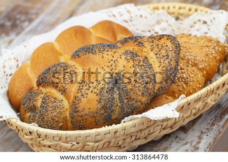 Challah bread with poppy seeds, sesame seeds and plain in bread basket  - stock photo