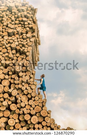 Challenge - Young man climbing the large pile of cut wooden logs - stock photo