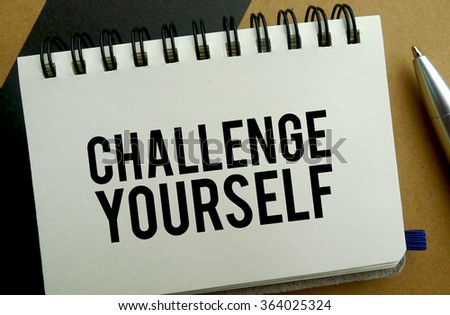 Challenge yourself memo written on a notebook with pen - stock photo