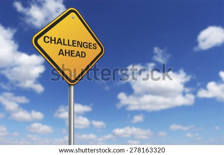 challenges ahead road sign and blue sky - stock photo