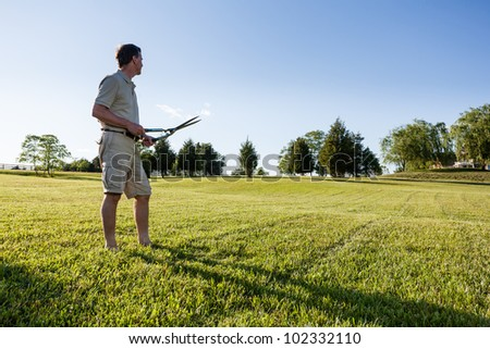 Challenging task of cutting large lawn with grass shears by hand