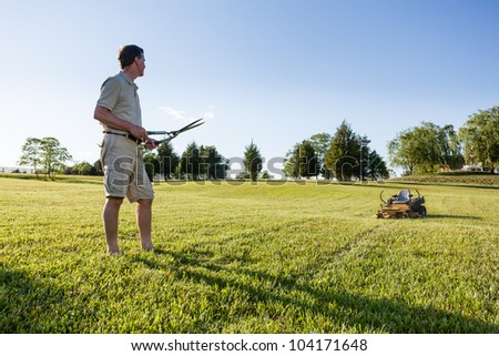 Challenging task of cutting large lawn with grass shears by hand with mower in background - stock photo