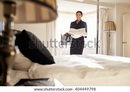 Chambermaid carrying linen in hotel bedroom, low angle view - stock photo